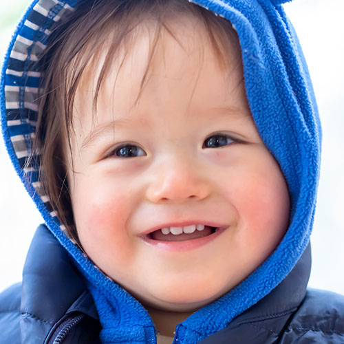 Happy toddler boy bundled up in winter clothes at a Preschool & Daycare Serving Albuquerque NM
