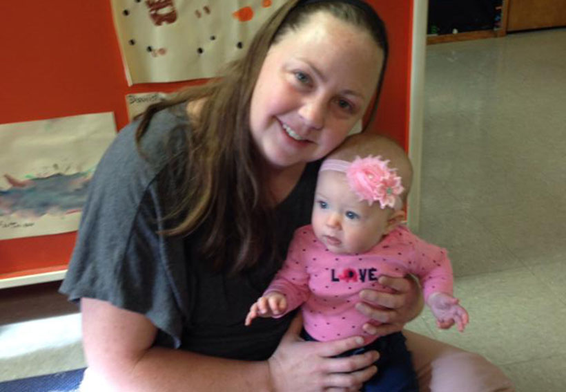 smiling teacher with infant at a Preschool & Daycare Serving Albuquerque NM