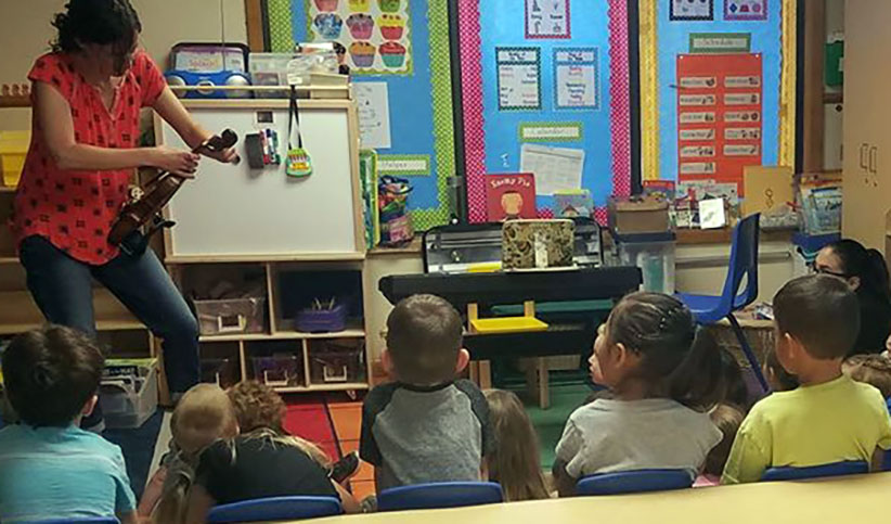 teacher playing violin for children at a Preschool & Daycare Serving Albuquerque NM