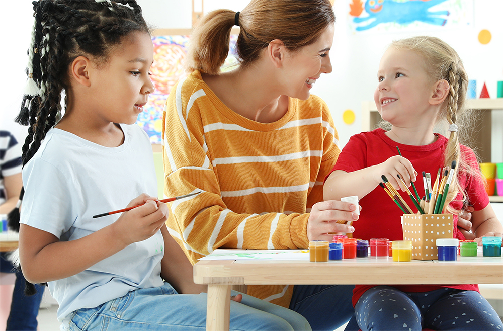 Children with female teacher at painting lesson indoors at a Preschool & Daycare Childcare Center serving Albuquerque NM.