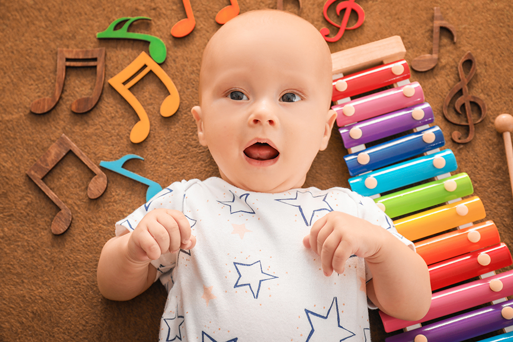 cute infant with musical instruments at a Preschool & Daycare Childcare Center serving Albuquerque NM
