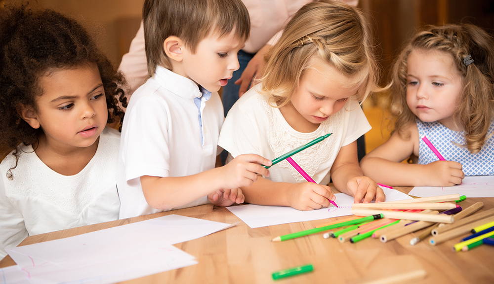 multicultural kids drawing in kindergarten at a Preschool & Daycare Childcare Center serving Albuquerque NM.